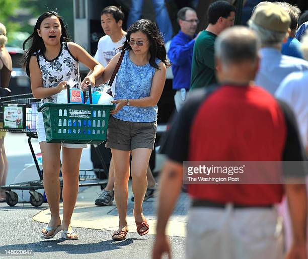 Cindy Chung carried a basket with two tenpound bags of ice with her from her mother Janet Chung at the Harris Teeter's free ice distribution to...