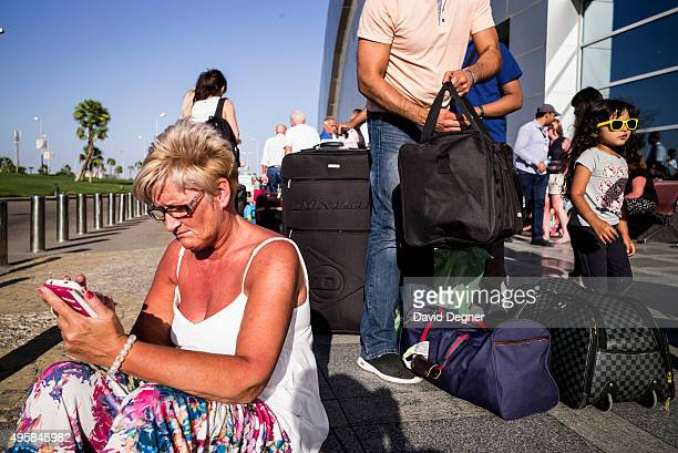 Cindy Crawford from near Glasgow Scotland sits on the sidewalk outside the terminal waiting for more information on a flight on November 05 2015 in...