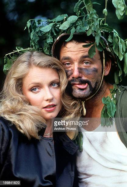 Cindy Morgan and Bill Murray nestled behind a tree in a scene from the film 'Caddyshack' 1980