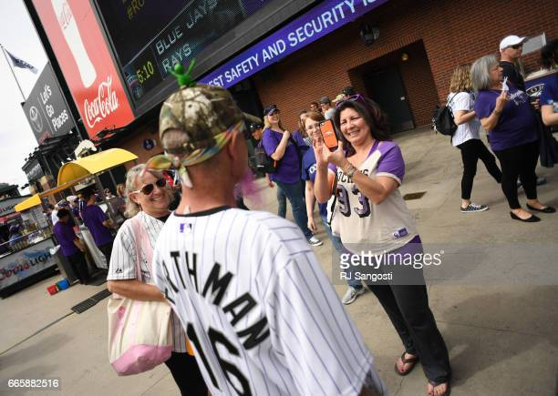 Cindy Torreslorett takes a photo of Brent Doeden aka 'Captain Earthman' and his wife Becky Scharfenberg arrive to Coors Field for the Colorado...