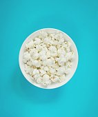 White fluffy movie theater popcorn in a bowl on blue background, top view