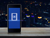 Play button with movie icon on modern smart phone screen on wooden table over blur colorful night light city tower, Cinema online concept