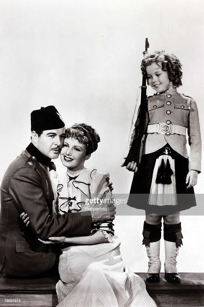 Cinema Personalities American 'child star' film actress Shirley Temple dressed as a kilted soldier girl is pictured with costars Michael Whalen and...
