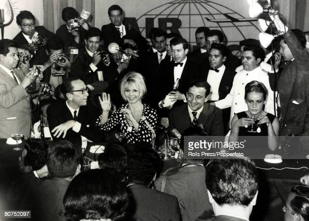 22nd January 1965 French film actress Brigitte Bardot pictured with her costar Jeanne Moreau right and Director Louis Malle as they are beseiged by...