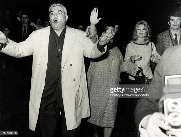 27th October 1963 French film actress Brigitte Bardot pictured in London protected by an escort including arm waving film producer Ardan as...