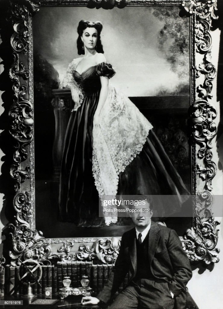 circa 1940's American film producer David O Selznick sits on a desk in front of a giant portrait of Vivien Leigh playing 'Scarlett O'Hara' in the...