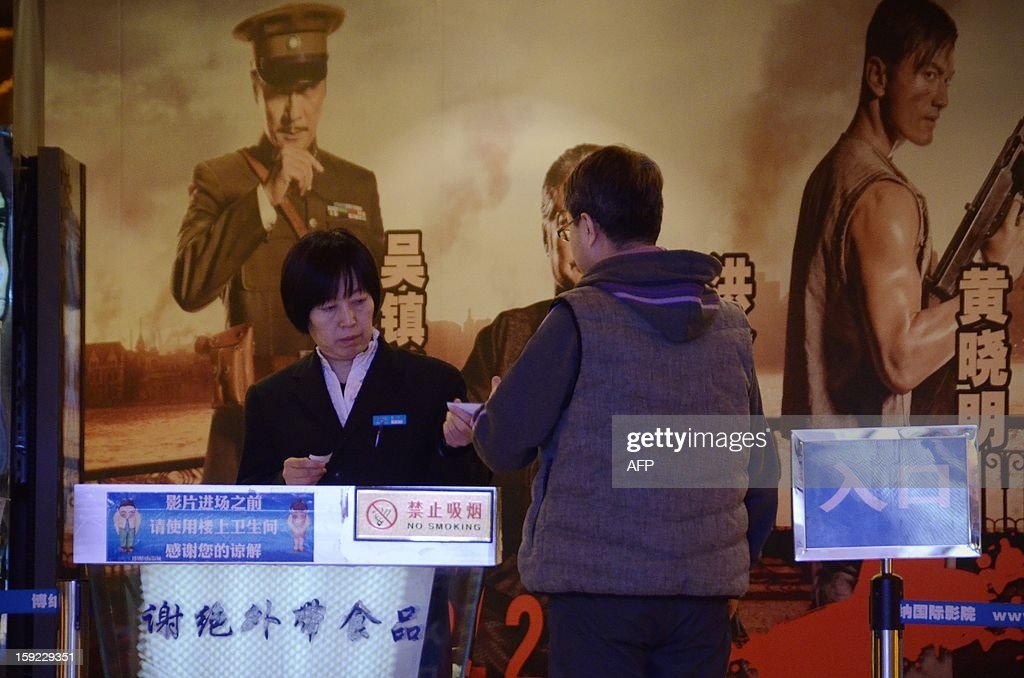A cinema staff member (L) checks a customer's ticket at the entrance of the movie house of a cinema in Beijing on January 10, 2013. Moviegoers in China spent 17 billion yuan (2.7 billion USD) on tickets last year, turning the country into the second-largest film market in the world, the state news agency Xinhua said on January 9.