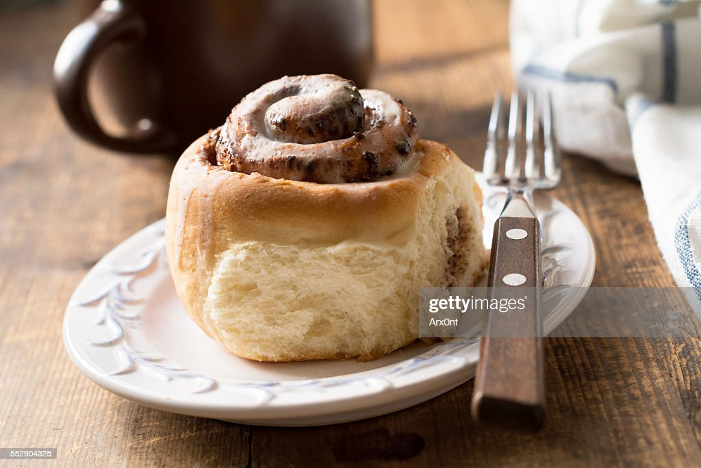 Cinnamon bun with cup of coffee, close up