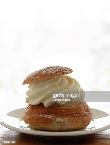 Cinnamon bun with whipped cream on plate