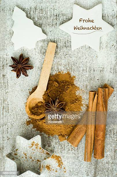 Cinnamon sticks with ground cinnamon, star anise and cookie cutter on a wooden table