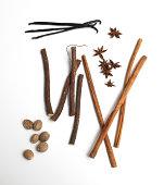 Cinnamon, vanilla, nutmeg, star anise and sugar cane against white background