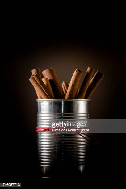 Cinnamons In Metal Container Against Colored Background
