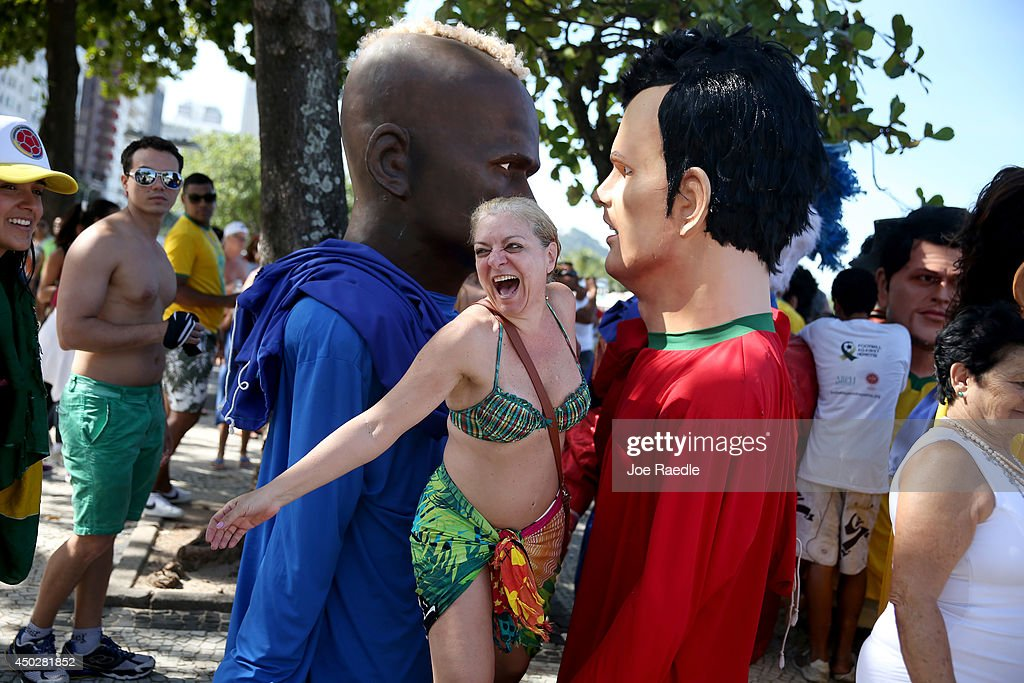 Cintya Mello laughs as she stands among large puppets in the likeness of soccer players during a break in a campaign against hepatitis parade featuring puppets of soccer stars and other celebrities on June 8, 2014 in Rio de Janeiro, Brazil. Brazil continues to prepare to host the World Cup which starts on June 12th and runs through July 13th.