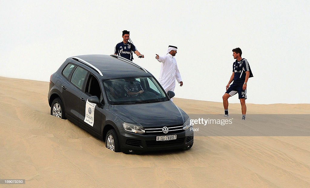 Ciprian Marica (L) and Klaas-Jan Huntelaar of Schalke stand next to a VW Touareg during a trip to the desert outside Doha at the Schalke 04 training camp on January 7, 2013 in Doha, Qatar.
