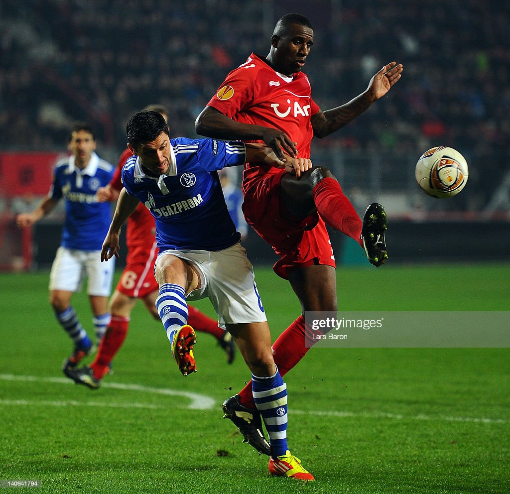 Ciprian MArica of schalke is challenged by Douglas of Twente during the UEFA Europa League Round of 16 first leg match between FC Twente and FC Schalke 04 on March 8, 2012 in Enschede, Netherlands.