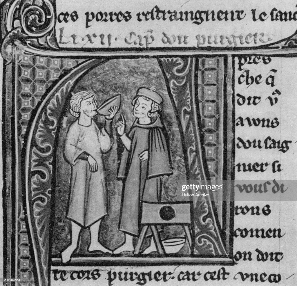 Circa 1400 A medieval patient drinking a potion prescribed by his doctor