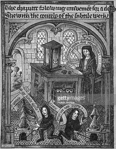 Circa 1450 A Fifteenth century alchemist is seated at a small table upon which stand a pair of scales in the foreground two boys attend to ovens