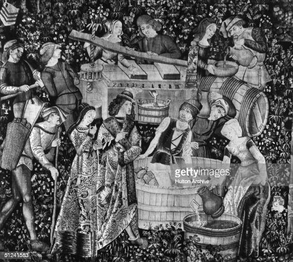 Circa 1500 French tapestry depicting noblemen and women treading and pressing grapes to make wine Original Publication From a set of tapestries on...