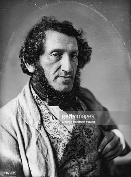 Studio portrait of an unidentified man with mutton chop beard and sideburns wearing a jacket a brocade vest with a floral pattern and a cravat The...