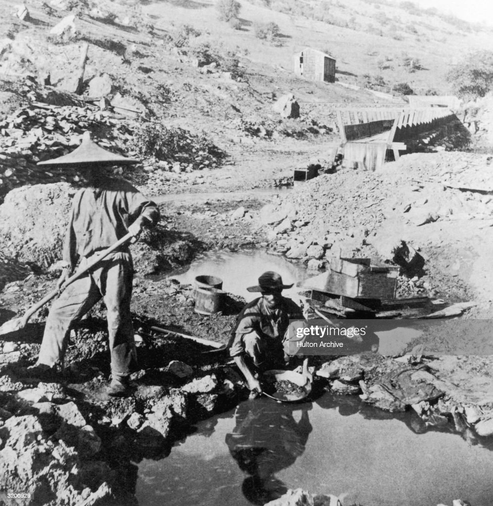 Chinese workers panning for gold in California A man in a coolie hat digs as another man kneels and sifts
