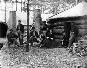 A woman and soldiers sitting outside a log cabin