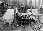 Confederate soldiers enjoying a game of poker a drink and a pipe at their camp site