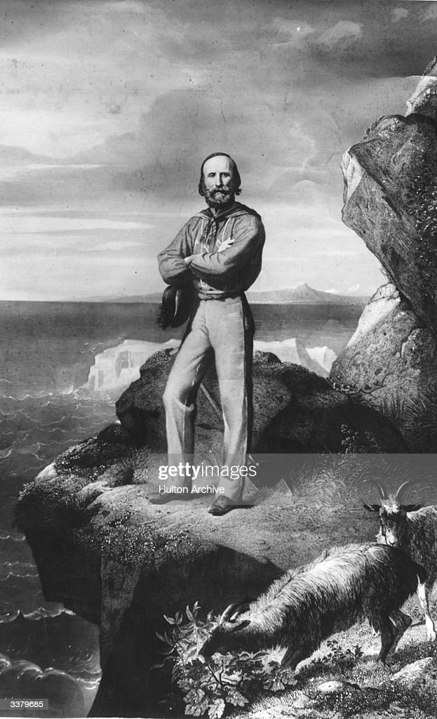 Italian patriot Giuseppe Garibaldi (1807 - 1882), founder of the 'Red Shirts' standing on a rocky cliff on the Isle of Caprera, next to a mountain goat.