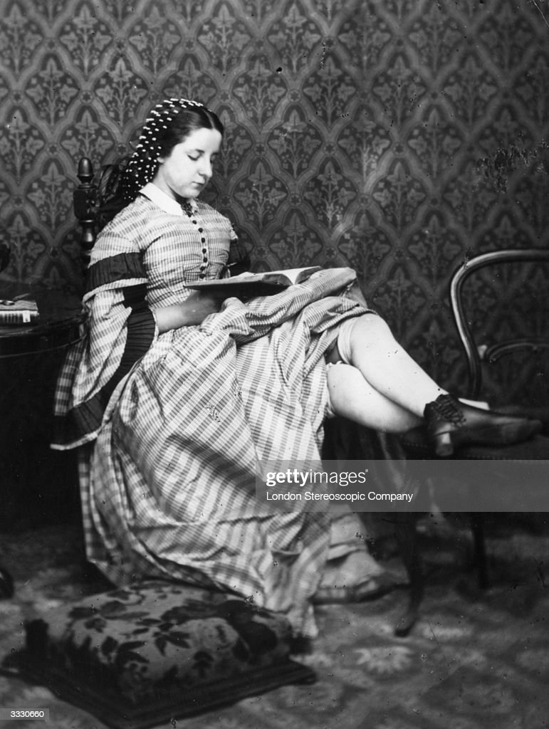 A Victorian girl reads a book her skirts hitched up to show her thick knee length stockings London Stereoscopic Company Comic Series