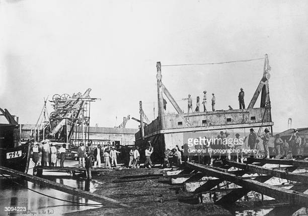 Workers operating dredging equipment during the construction of the Suez Canal at Port Said
