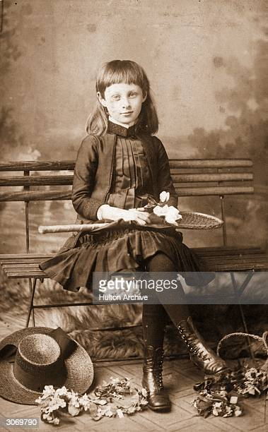A young girl sits on a bench holding a tennis racquet She wears a dress with a pleated bodice long sleeved jacket black woollen stockings and button...