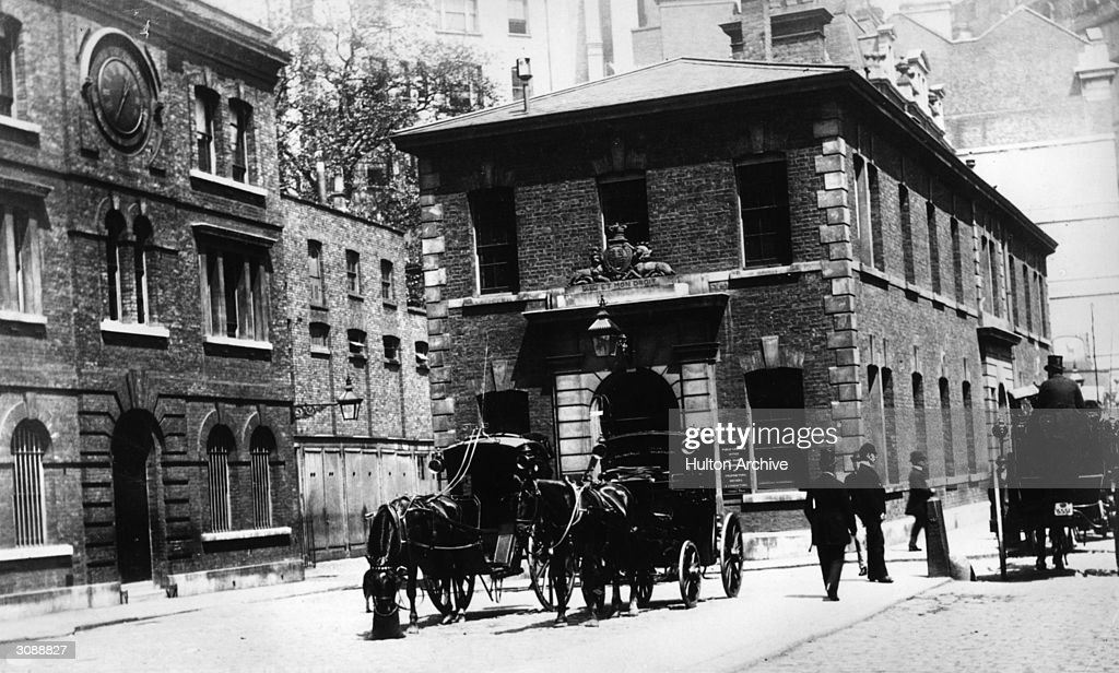 On the left Scotland Yard in the centre with horse drawn cabs outside is the Public Carriage Office