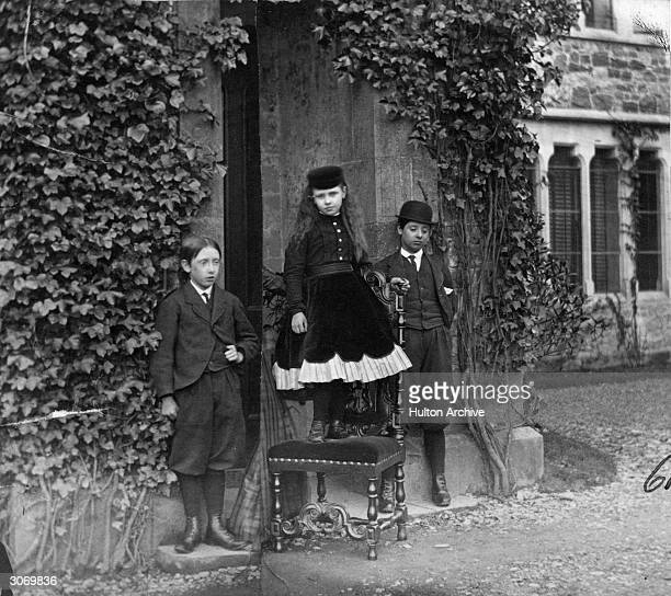 Three Victorian children outside their country home