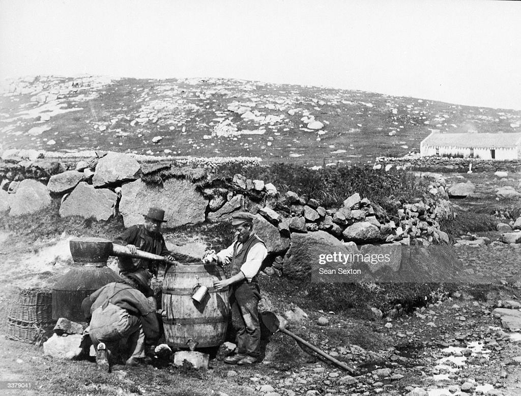 Irish men watching the Poteen still in Connemara, County Galway. Poteen is alcohol made illegally from potatoes.