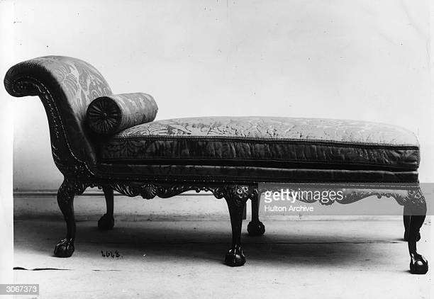 A carved chaise longue with a bolster pillow