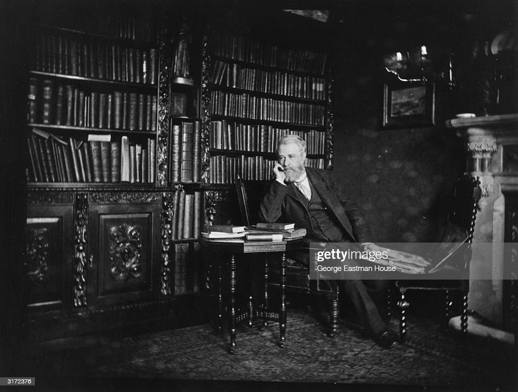 A full-length portrait of British photographer Henry Peach Robinson (1830 - 1901) leaning his elbow on some books while seated in a library.