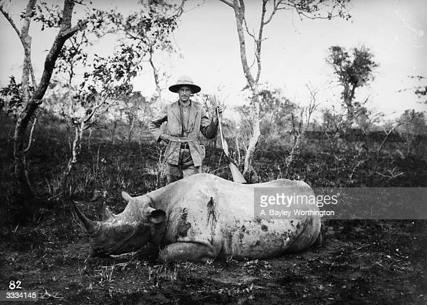 A hunter with a rhinoceros he has killed