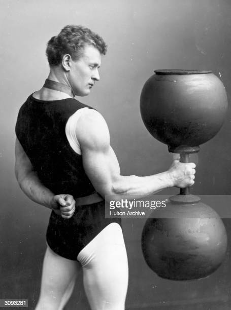 German strongman Eugene Sandow lifting a large dumbbell