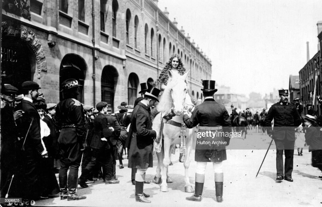 Lady Godiva mounts a fine white horse for a pageant in Coventry and a crowd of people look on