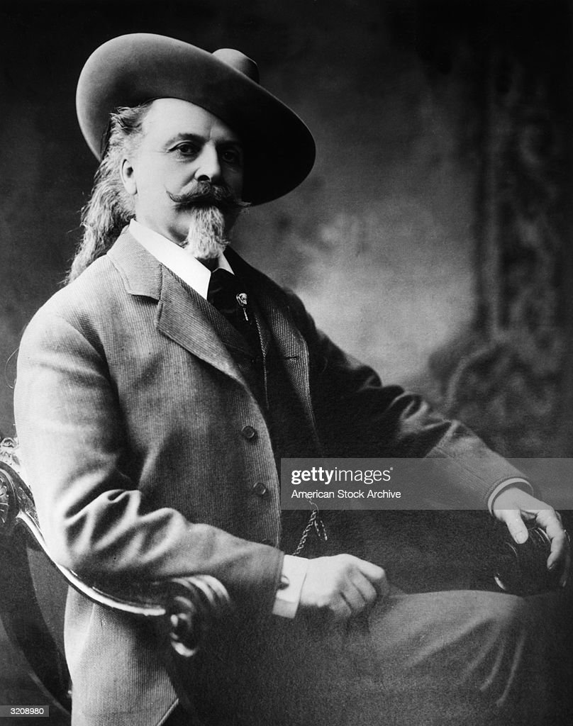 Studio portrait of American frontiersman and entertainer William 'Buffalo Bill' Cody wearing a threepiece suit sitting in a chair