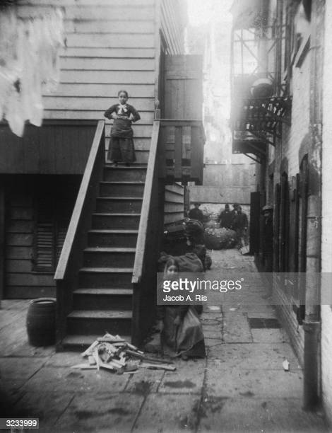 Two young girls both ragpickers stand at a staircase in Baxter Alley Little Italy New York City The alley was known as 'Ragpickers Row'
