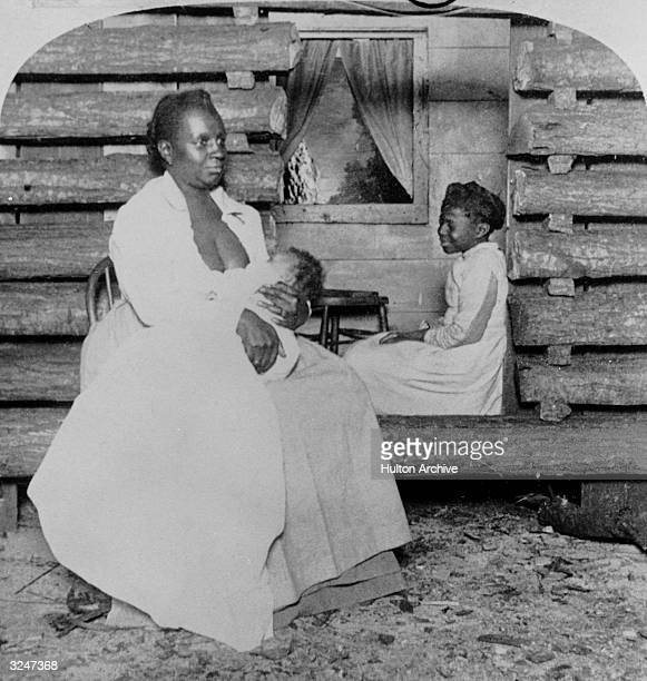 An AfricanAmerican woman holds an infant while an older child sits inside a log cabin