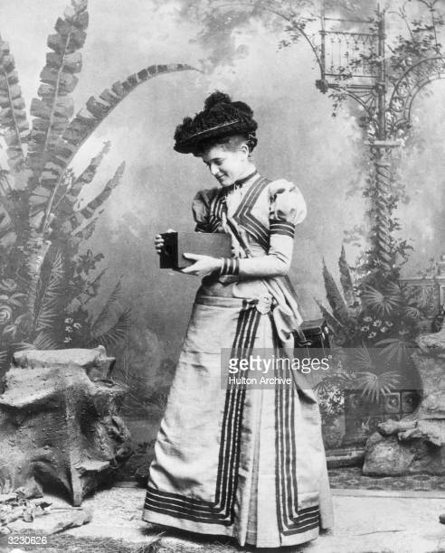A woman holding an early Kodak camera which was sold with the film already loaded The entire camera was returned to the factory for film processing