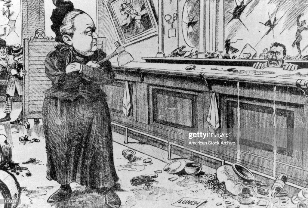 Editorial cartoon depicting American temperance activist Carry Nation (Amelia B Moore, 1846 - 1911) glaring at a terrified bartender as she holds a hatchet in a saloon.