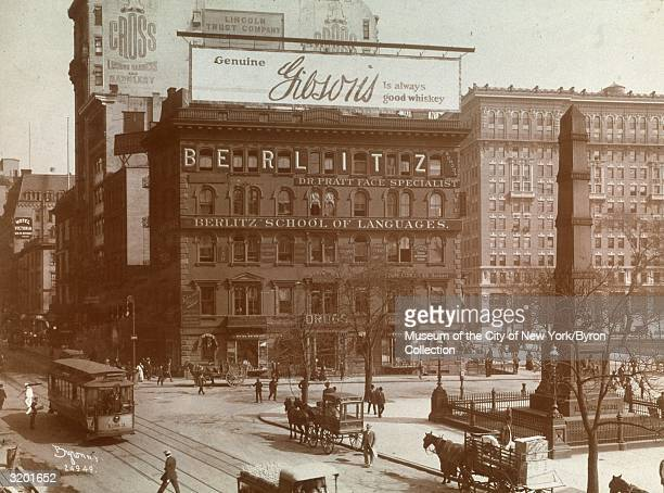 Fulllength view of pedestrians trolley cars and horsedrawn carriages passing the Berlitz School of Languages and the monument at Madison Square...