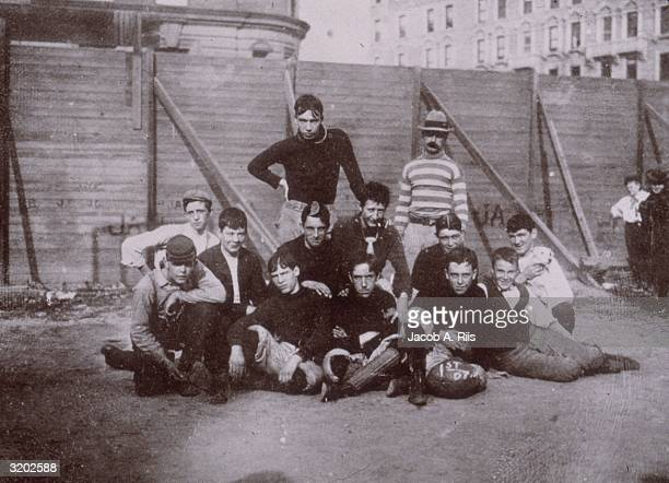 Group portrait of a football team posing in front of a fence at the West Side Playground 68th Street New York City