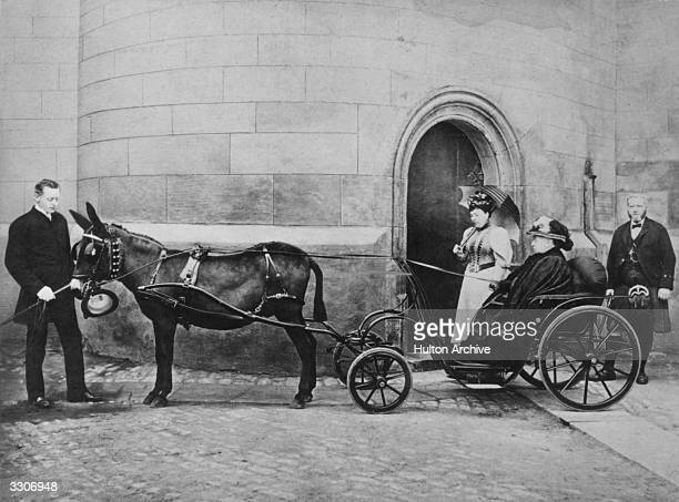 Queen Victoria in a small donkeydrawn carriage at Balmoral with her youngest daughter Princess Beatrice John Brown wearing a kilt stands behind her...