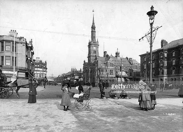 A child with a pram on the streets of Blackpool with the Town Hall in the background