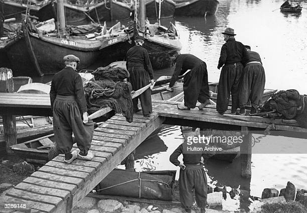 A group of Dutch workmen wearing wooden clogs prepare to load a boat