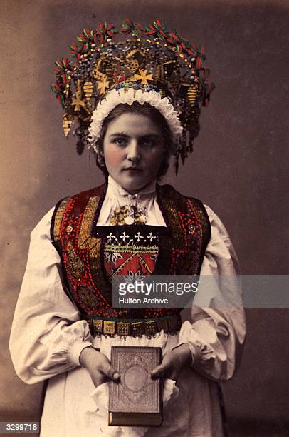 A Norwegian bride wearing traditional wedding costume an embroidered bodice and elaborate headdress