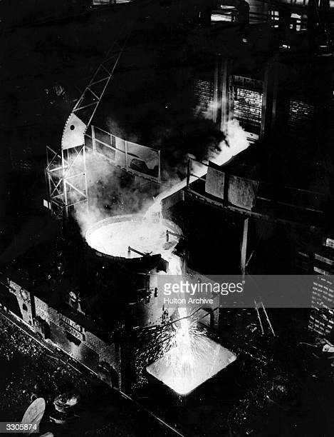 An iron foundry for the making of rails at Crewe during production with hot metal flowing from the furnace onto the ladle